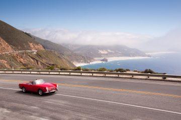 Red car on coastal highway